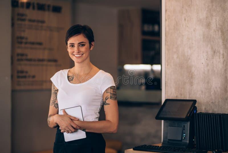 Camarera de sexo femenino que trabaja en un restaurante foto de archivo libre de regalías
