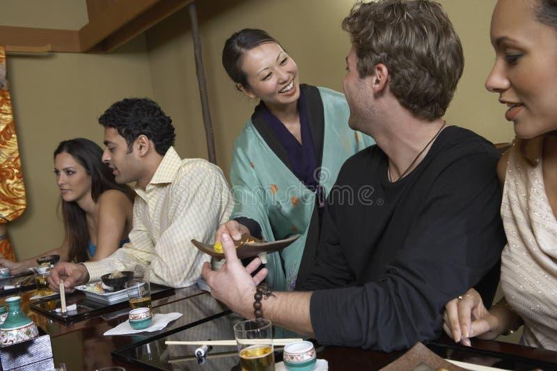 Camarera de sexo femenino Serving Food imagen de archivo