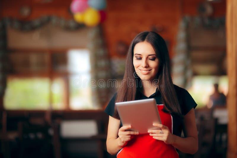Camarera del restaurante con órdenes de manejo de la tableta de la PC fotos de archivo