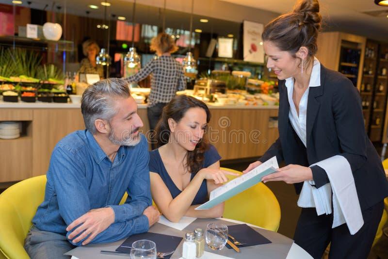 Camarera del restaurante que da el menú a los clientes fotos de archivo