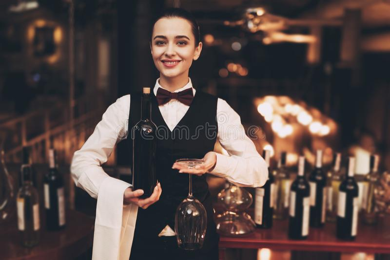 Camarera elegante alegre que sostiene la botella de vino rojo y de vidrios, barra cercana permanente imagen de archivo libre de regalías