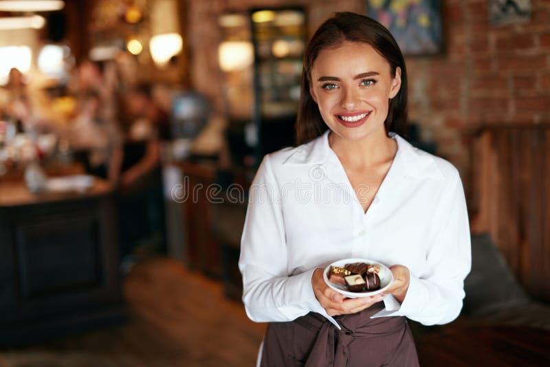 Camarera en café Mujer con los caramelos de chocolate en confitería fotos de archivo libres de regalías