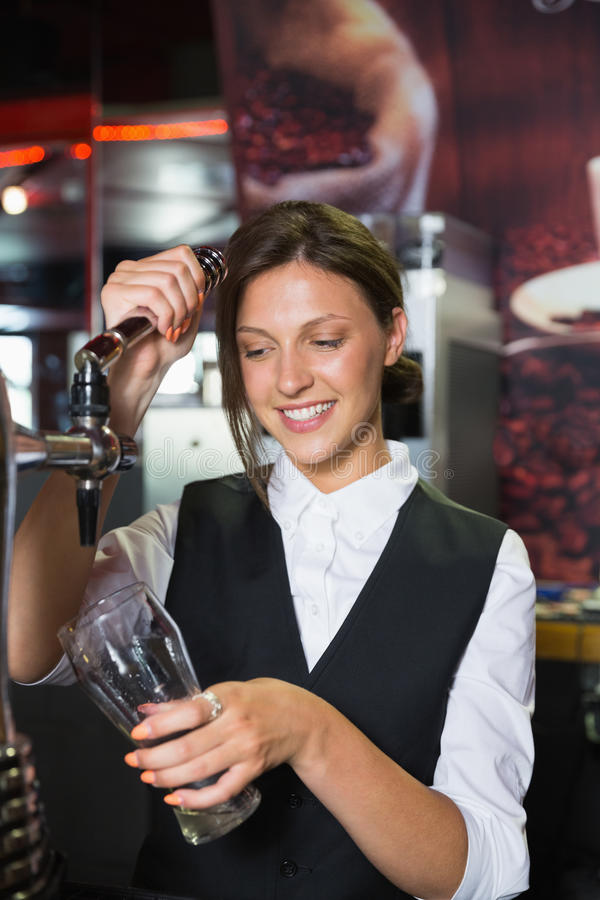 Camarera feliz que tira de una pinta de cerveza fotos de archivo libres de regalías
