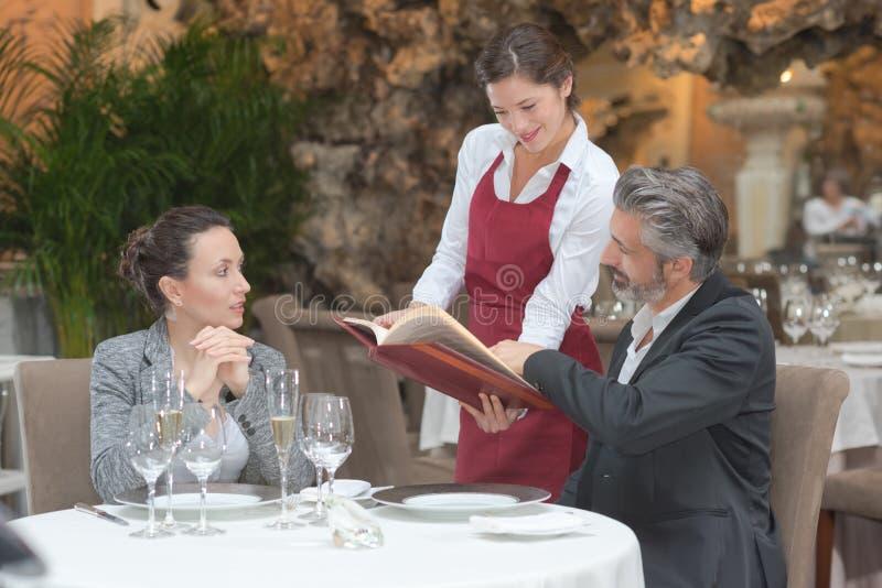 Camarera hospitalaria que toma orden de los pares en restaurante de la gastronomía fotos de archivo libres de regalías