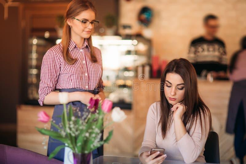 Camarera joven atractiva que usa una tableta para tomar una orden de un cliente en una cafetería imagenes de archivo