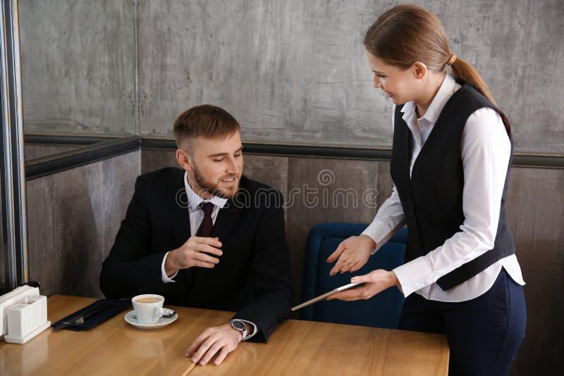 Camarera joven con el menú en la pantalla de la tableta en restaurante imagenes de archivo