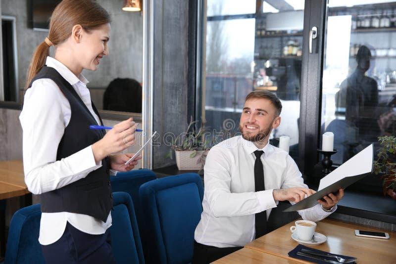 Camarera joven que toma una orden del hombre en restaurante fotos de archivo