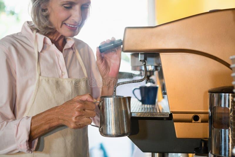 Camarera mayor que usa la cafetera fotografía de archivo libre de regalías