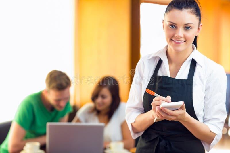 Camarera que escribe una orden con los estudiantes que usan el ordenador portátil en la cafetería fotografía de archivo libre de regalías