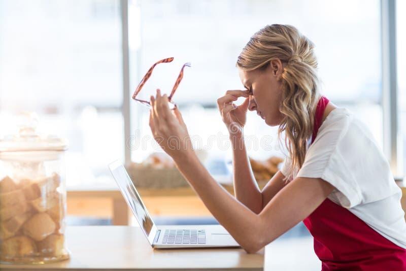 Camarera que se sienta en la tabla y que usa el ordenador portátil en café foto de archivo libre de regalías