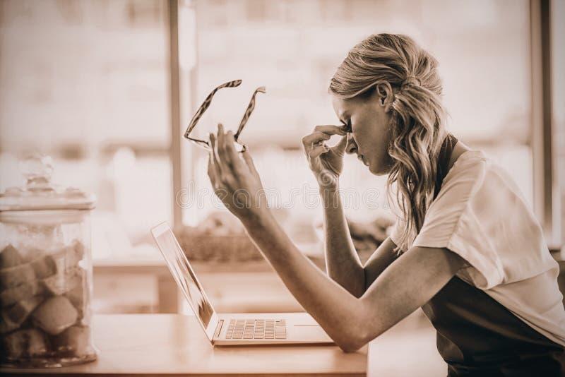 Camarera que se sienta en la tabla y que usa el ordenador portátil en café foto de archivo