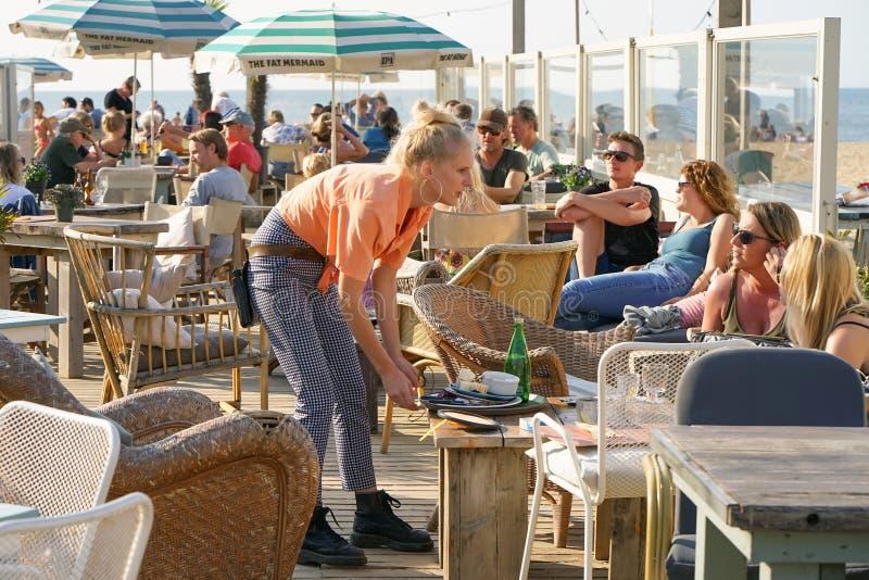Camarera que sirve a un cliente en el restaurante, café, barra de la playa imágenes de archivo libres de regalías