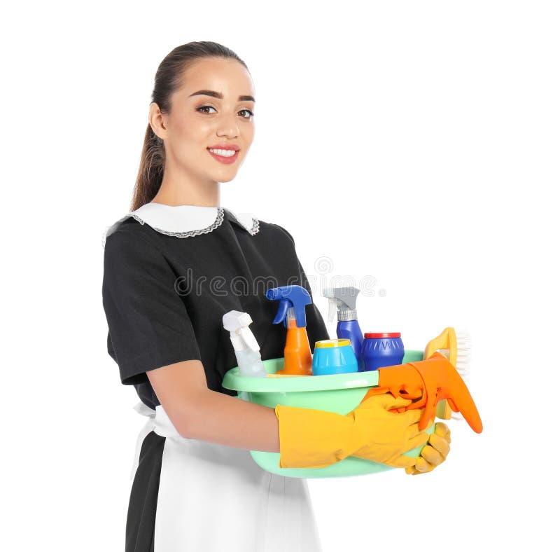 Camarera que sostiene el lavabo plástico con los detergentes en el fondo blanco imagenes de archivo