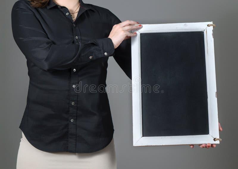 Camarera que sostiene la pizarra vertical fotos de archivo
