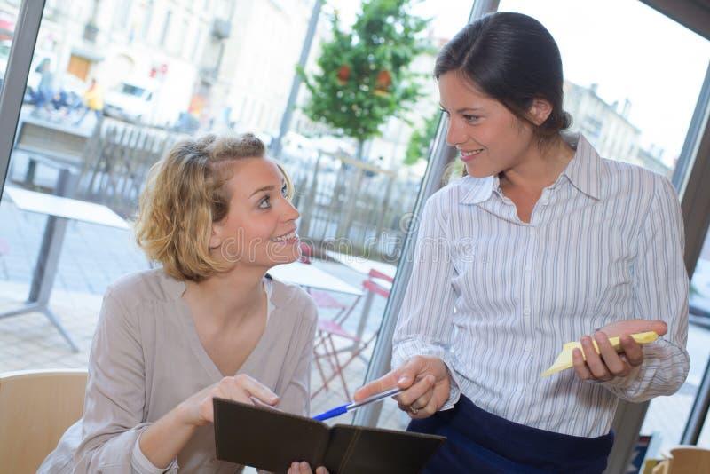 Camarera que toma orden del cliente femenino en café foto de archivo