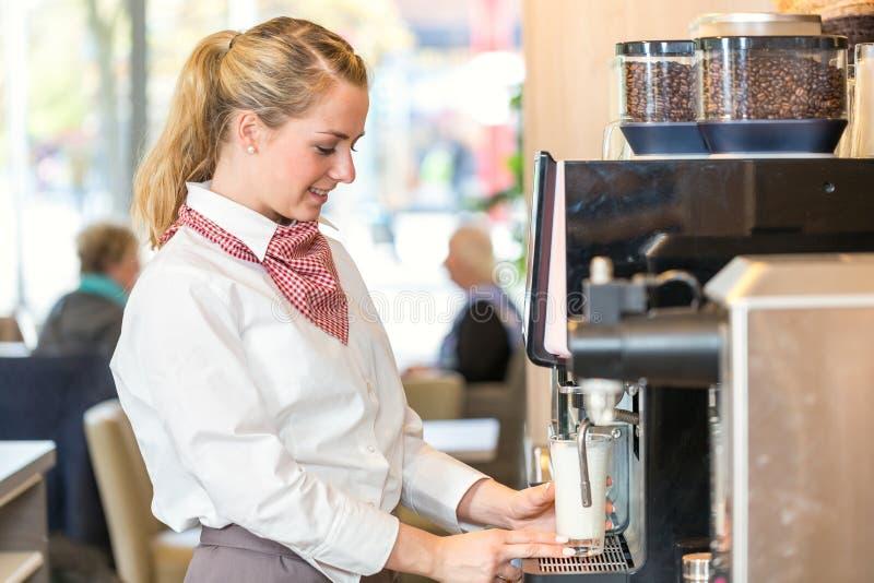 Camarera que trabaja en la máquina del café en panadería o café imagenes de archivo