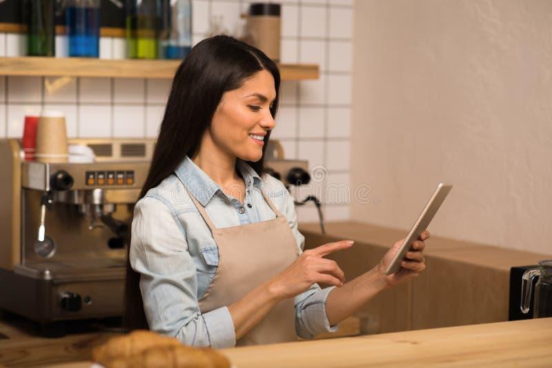 Camarera que usa la tableta digital en café imagenes de archivo