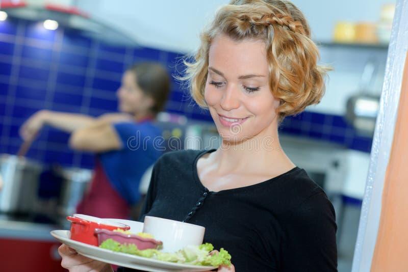 Camarera rubia joven que sostiene la placa de la cocina fotografía de archivo libre de regalías