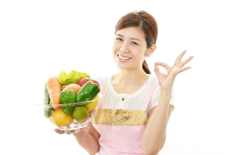 Camarera sonriente que sostiene verduras fotografía de archivo libre de regalías