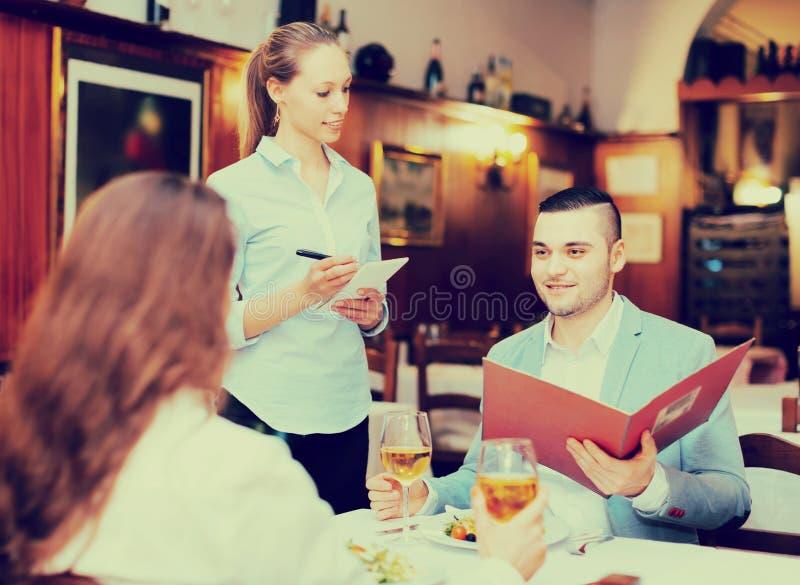 Camarera y huéspedes en café fotos de archivo