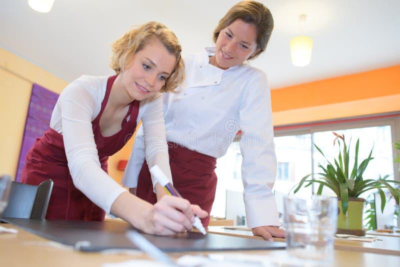 Camareras jovenes que escriben en el tablero del restaurante imagenes de archivo