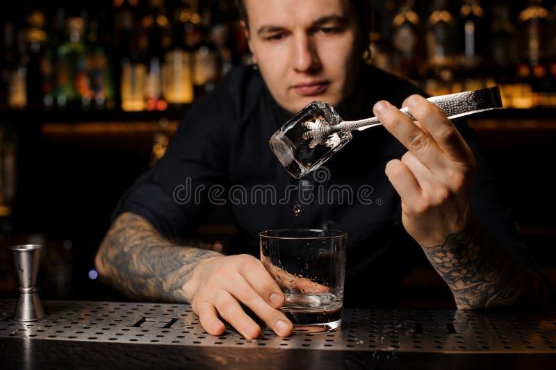 Camarero atractivo que añade a una bebida alcohólica en el vidrio un cubo de hielo grande foto de archivo