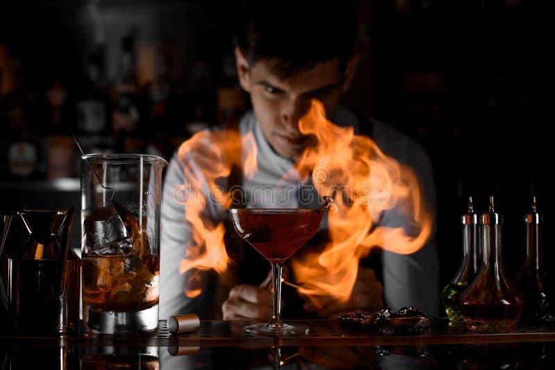 Camarero atractivo que mira en el fuego alrededor del vidrio de cóctel imagen de archivo libre de regalías