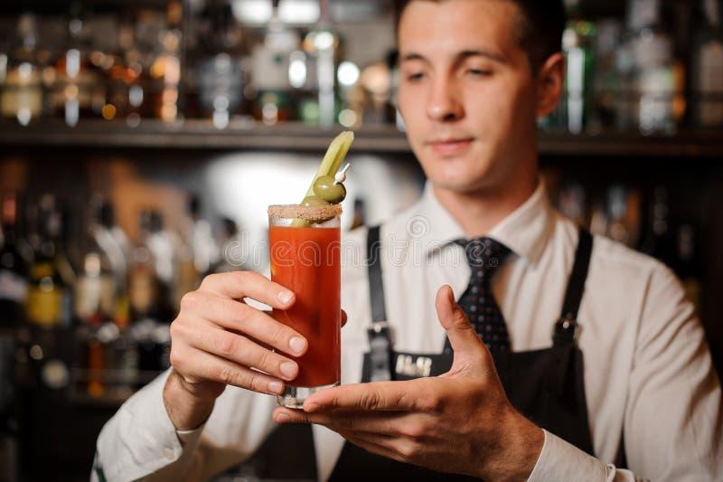 Camarero atractivo que sostiene un cóctel del bloody mary con dos aceitunas y apios foto de archivo