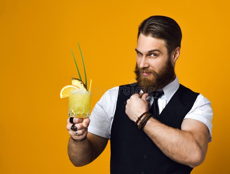 Camarero barbudo con el cóctel de la tenencia de la barba en chaleco foto de archivo libre de regalías