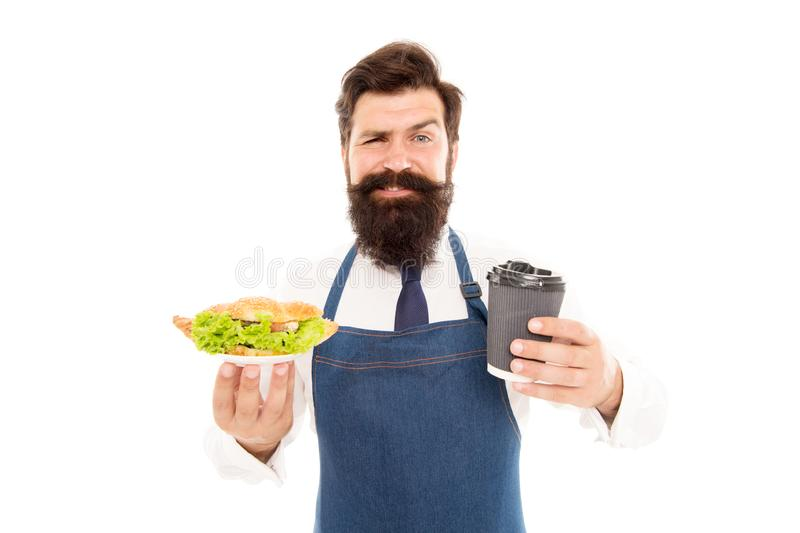 Camarero barbudo del hombre que da la placa con la taza de la comida y de café Croissant delicioso Concepto de la comida del café imagen de archivo
