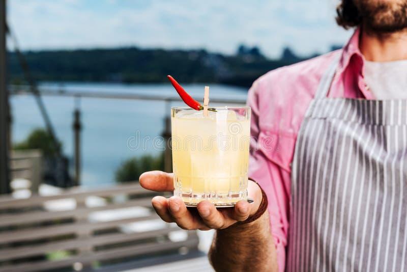 Camarero barbudo que muestra a vidrio de la bebida del alcohol su cliente fotos de archivo