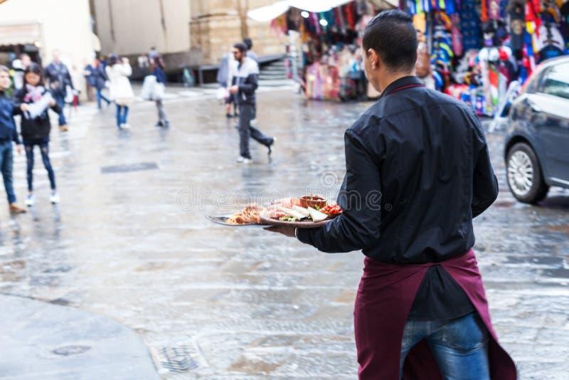 Camarero con las placas con la comida italiana adentro al aire libre foto de archivo