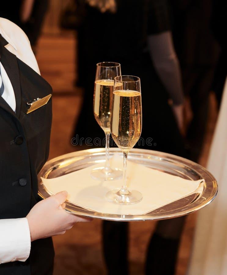 Camarero de sexo femenino con las flautas de champán imagen de archivo libre de regalías