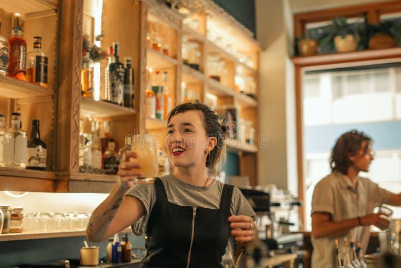 Camarero de sexo femenino joven sonriente que hace los cócteles en una barra imagen de archivo
