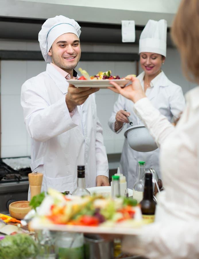 Camarero de sexo femenino que toma el plato en la cocina fotografía de archivo