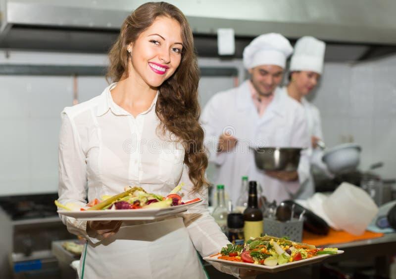 Camarero de sexo femenino que toma el plato en la cocina imagen de archivo