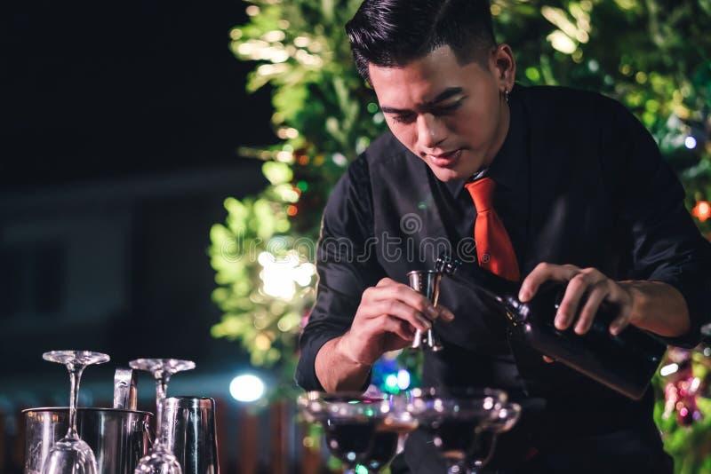 Camarero de sexo masculino asiático profesional preparar la bebida de mezcla del cóctel en el pueblo imagen de archivo