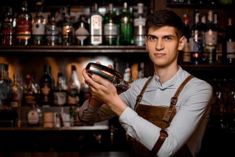 Camarero de sexo masculino atractivo que sostiene en manos una coctelera de acero fotos de archivo
