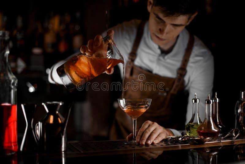 Camarero de sexo masculino atractivo que vierte un cóctel alcohólico marrón de la taza de medición al vidrio en la oscuridad imágenes de archivo libres de regalías
