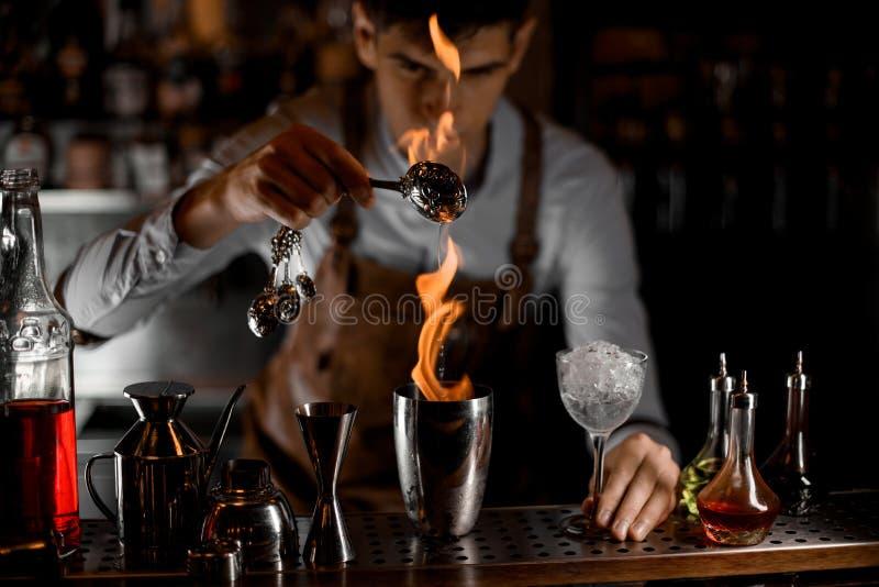Camarero de sexo masculino atractivo que vierte una esencia de la cuchara en la llama a la coctelera de acero imagenes de archivo