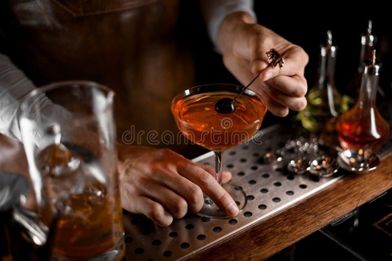 Camarero de sexo masculino que pone la baya en el pincho sobre el vidrio de cóctel imágenes de archivo libres de regalías
