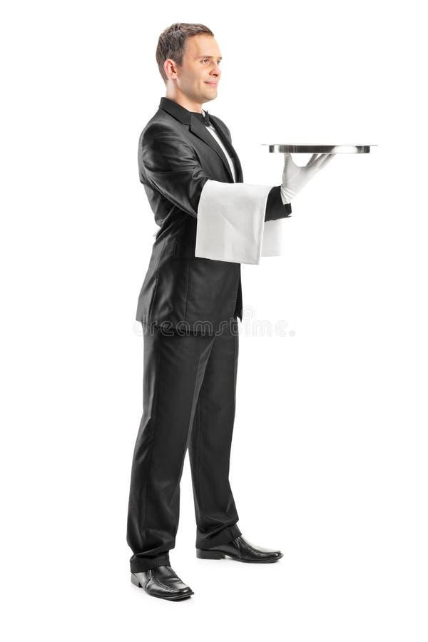 Camarero de sexo masculino que sirve y que sostiene una bandeja fotografía de archivo libre de regalías
