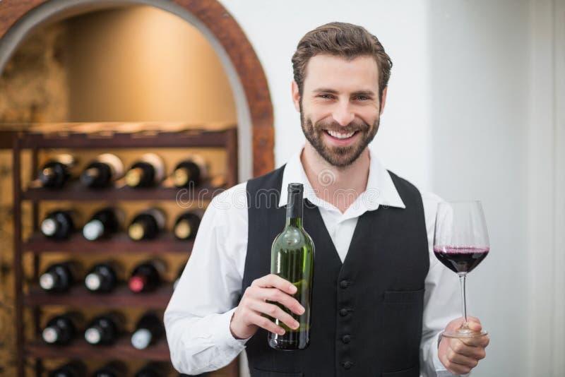 Camarero de sexo masculino que sostiene la botella de la copa de vino y de vino en el restaurante imagenes de archivo