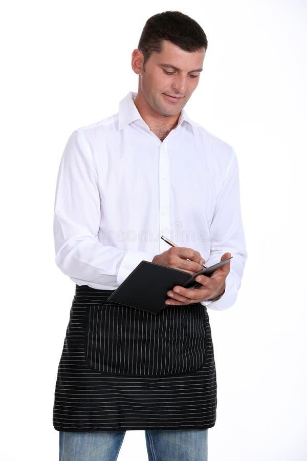 Camarero de sexo masculino que toma orden imagen de archivo