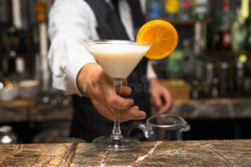 Camarero en el trabajo, preparando los cócteles Colada del pina de la porción foto de archivo