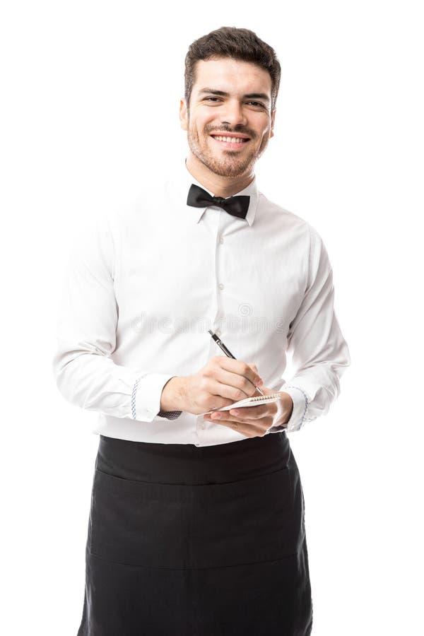Camarero feliz de tomar su orden imagen de archivo libre de regalías