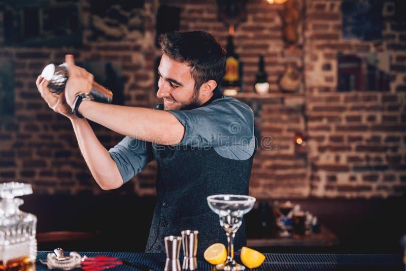 camarero feliz que usa la coctelera para la preparación del cóctel El retrato del camarero que hacía tequila basó el margarita en fotos de archivo libres de regalías