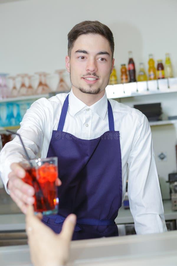 Camarero joven amistoso que sirve la bebida cordial al cliente fotos de archivo
