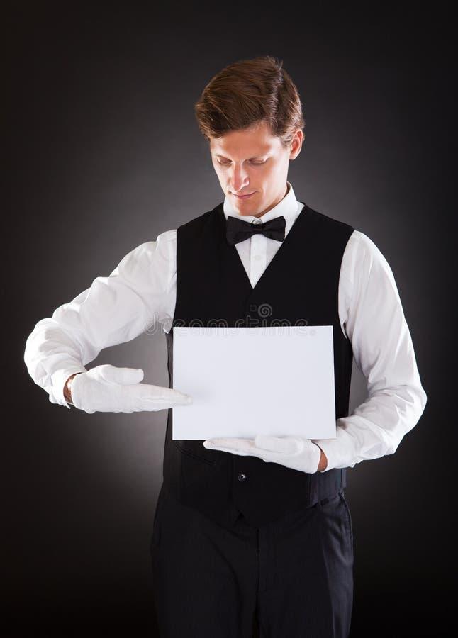Camarero joven que lleva a cabo el cartel en blanco fotografía de archivo libre de regalías
