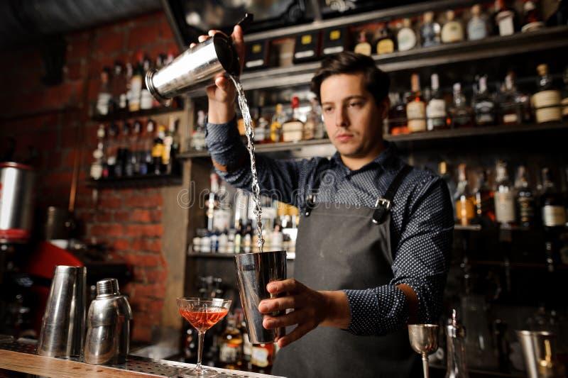 Camarero joven que vierte la bebida alcohólica a partir de un vidrio del metal en otro imagen de archivo libre de regalías